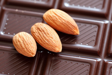 Three almonds on chocolate background