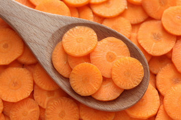 Slices of fresh carrot in a wooden spoon