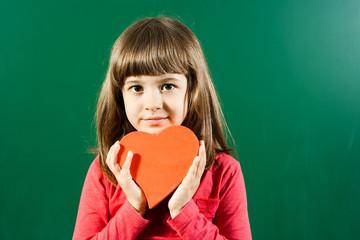 Cute little girl holding heart shape in front of blackboard