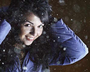 winter portrait of a brunette on a black background