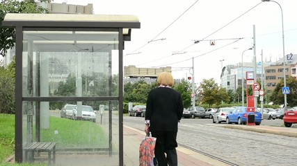 empty tram stop - old woman walking around