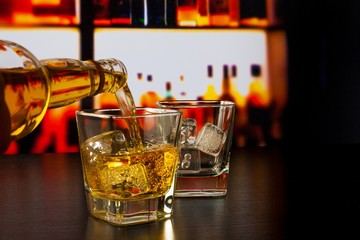 barman pouring whiskey in front of whiskey glass and bottles