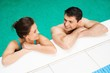 Young cheerful couple relaxing in a swimming pool