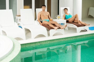 Couple relaxing with refreshing drinks near swimming pool