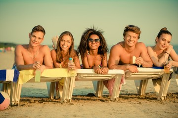 Group of multi ethnic friends sunbathing on a beach