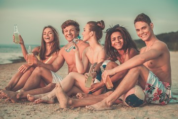 Group of multi ethnic friends with drinks sitting on a beach