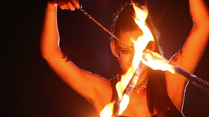 Artist turns the fire fans and snakes in performance