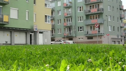 high rise block of flats with green grass a parked cars