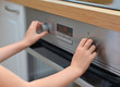 Child playing with electric oven.