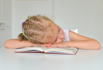 Sleeping little girl with book on the table.