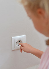 Child sticks his fingers in the socket. Dangerous situation.