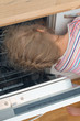 Little girl putting head into dishwasher.