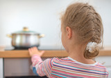 Little girl touches hot pan on the stove.