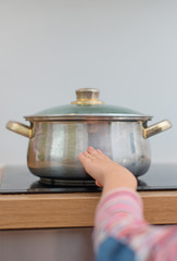 Child touches hot pan on the stove. Dangerous situation at home.