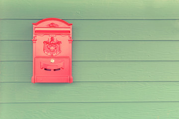 Red mailbox with green wood background. vintage style