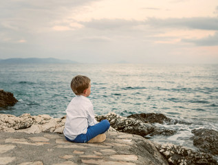 Little boy looks on the sunset sea landscape