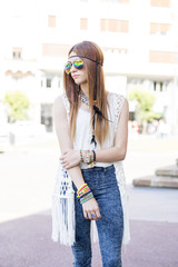 Elegant hippie style woman with sunglasses in the street.