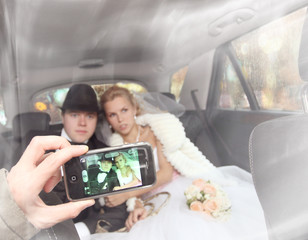 bride and groom are photographed on phone