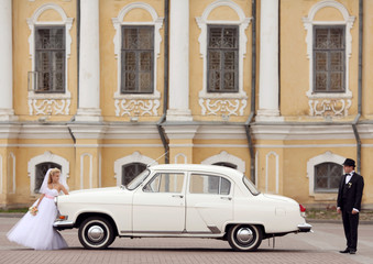 groom and bride in white vintage car