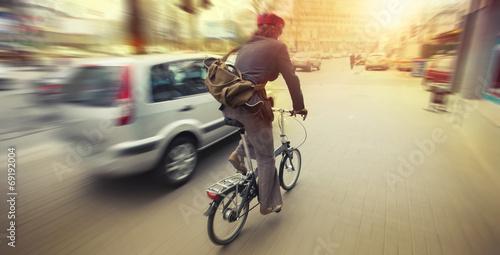 Leinwandbild Motiv cyclist in traffic on the city roadway motion blur