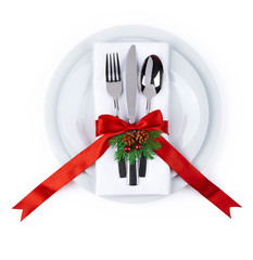 Christmas plate and silverware with red ribbon isolated on white