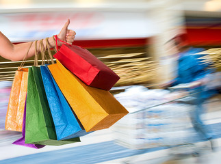 Woman holding shopping bags and gesturing thumb up