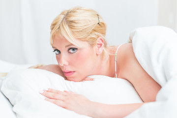 Beautiful blonde woman in the bed