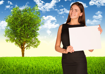 Businesswoman with tree and green landscape