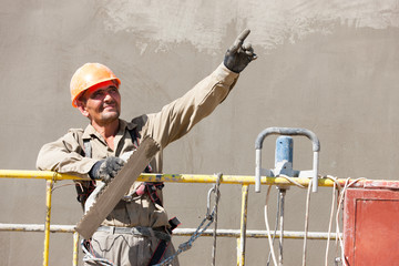 Plasterer worker showing at distance during Construction Works