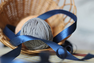 ball of gray threads with blue ribbon