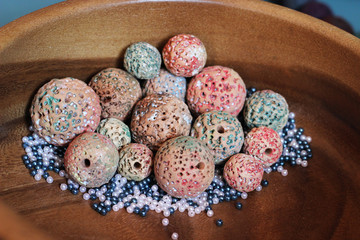 clay beads in wooden bowl