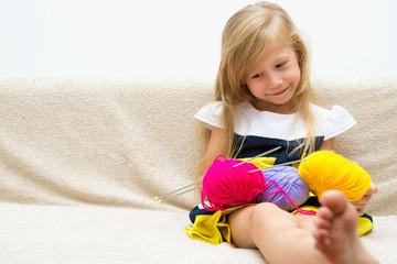 Портрет маленькой красивой девочки с пряжей