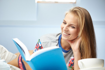 Young beautiful woman reading book  in bed
