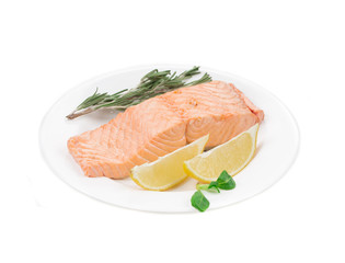 Fried salmon fillet with lemon and basil.