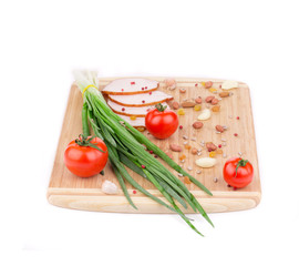 Fresh vegetables and ham on cutting board.