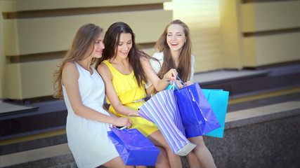 Three cute girls sitting to discuss th selected fashion items