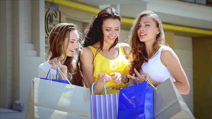 Three cute girls discuss their shopping outside the boutique