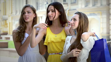 Three girls standing in front of a showcase discuss new dress