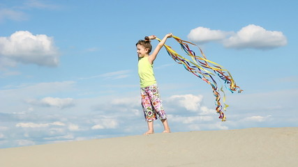 little girl with colorful ribbons on windy beach