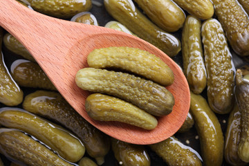 Pickled gherkins in a wooden spoon