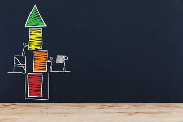 Stichmännchen bauen Turm auf einer Tafel