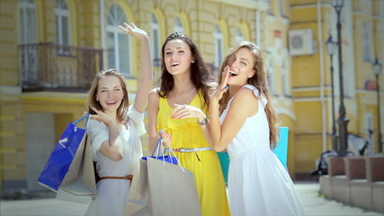 Three girls waving and attract attention holding shopping bags