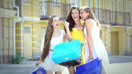 Three girls on a sunny afternoon walk with bags fashion shopping