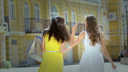 Two girls shopaholic carry bags with fashionable things