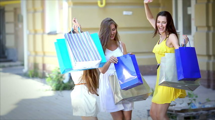 Girls jumping with delight bought fantastic fashionable things