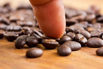 Coffee and finger on wooden background ,Concept select coffee be