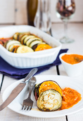 ratatouille sauce served in a round plate, fork, knife on a whit
