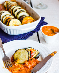 ratatouille in a round plate with sauce, knife, closeup