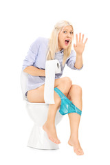 An interrupted girl sitting on a toilet