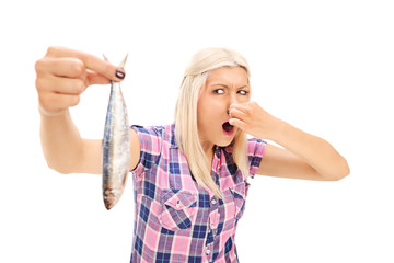Blond woman holding a stinky fish
